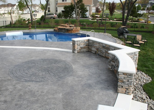 stamped concrete, cultured stone, retaining wall, white bullnose capping, natural stone pool waterfall