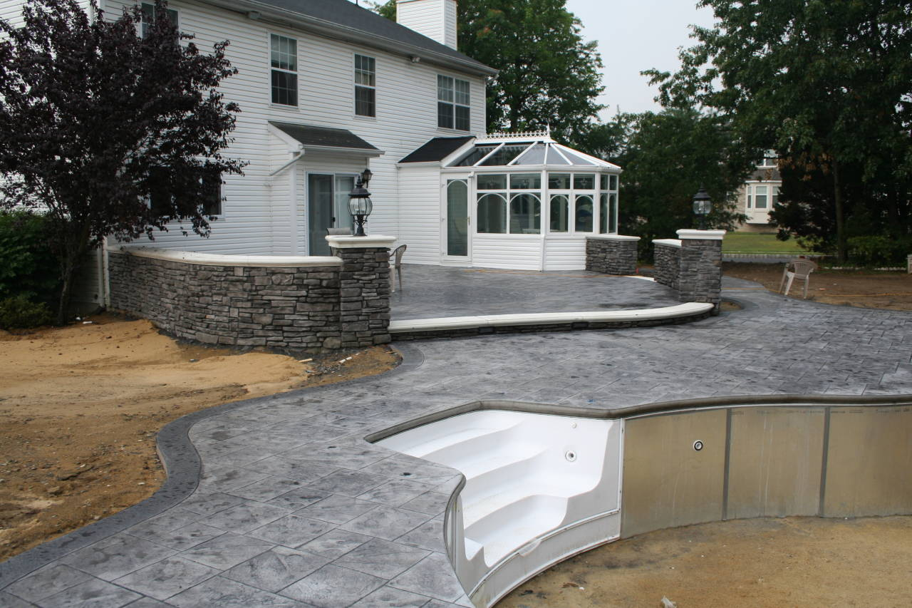 Installation of a new pool with a gray stamped concrete pool patio